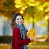 Girl in autumn park with golden foliage on a sunny fall day, holding yellow leaves in her hands. Beautiful young girl in autumn park with golden foliage on a stock photography