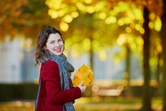 Girl in autumn park with golden foliage on a sunny fall day, holding yellow leaves in her hands. Beautiful young girl in autumn park with golden foliage on a stock photos