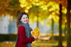 Girl in autumn park with golden foliage on a sunny fall day, holding yellow leaves in her hands. Beautiful young girl in autumn park with golden foliage on a royalty free stock photography