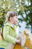 Girl in an autumn park on a horse. Little girl is playing with a toy horse in an autumn Royalty Free Stock Image