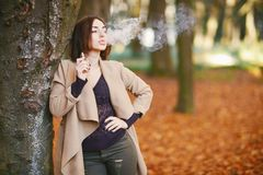Girl in the autumn park. Leaning on a tree and smoking from an electronic cigarette stock photo
