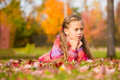 Girl in Autumn Park. Little girl lying on a colorful leaves in autumn park stock photo