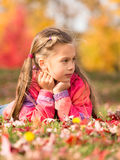 Girl in Autumn Park. Little girl lying on a colorful leaves in autumn park royalty free stock photos