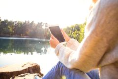 Girl in an autumn park near a lake holds a tablet. Girl in the nature Stock Photo