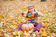 Girl in autumn park with pumpkin and apple Stock Image