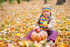Girl in autumn park with pumpkin and apples Royalty Free Stock Photo