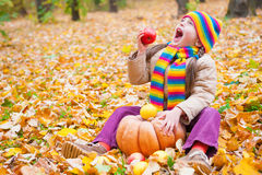 Girl in autumn park with pumpkin and apples Royalty Free Stock Image