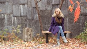 Girl in autumn park sitting on the bench. Beautiful blonde girl in purple coat in autumn park sitting on the bench and smiling, stone wall on background royalty free stock photography