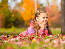 Girl in Autumn Park. Smiling little girl lying on a colorful leaves in autumn park stock photography