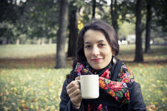 Girl in an autumn part with a white cup of hot drink. Beautiful girl in an autumn part with a white cup of hot drink Stock Photo