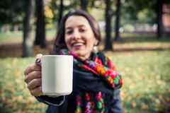 Girl in an autumn part with a white cup of hot drink. Beautiful girl in an autumn part with a white cup of hot drink Stock Image