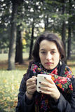 Girl in an autumn part with a white cup of hot drink Stock Image