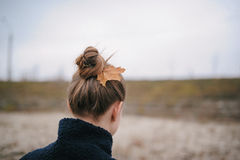 The girl during the autumn period with a maple leaf in hair Royalty Free Stock Photo