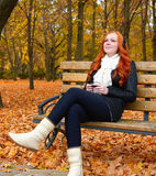 Girl in autumn season listen music on audio player with headphones, sit on bench in city park, yellow trees and fallen leaves Stock Photo