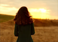 Girl in autumn at sunset standing in a field Stock Photo