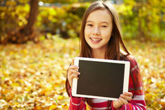 Girl in autumn with tablet computer Royalty Free Stock Photos