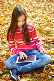 Girl in autumn with tablet computer Royalty Free Stock Image