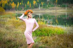 A girl in an autumn wreath. And a pink dress stands among the wilted grass. She is on the background of the lake stock photos