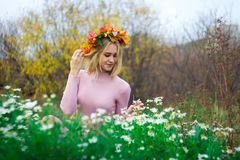 A girl in an autumn wreath. And a pink dress sits in the flowers of daisies stock photos