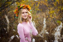 A girl in an autumn wreath. And a pink dress stands among the wilted grass stock photography