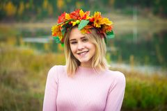 A girl in an autumn wreath. And a pink dress stands among the wilted grass. She is on the background of the lake stock photo