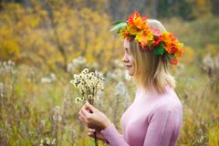 A girl in an autumn wreath. And a pink dress stands among the wilted grass. Dandelions in her hand royalty free stock images