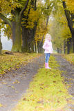 Girl in autumnal alley. Little girl wearing rubber boots in autumnal alley Stock Image