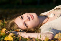 Girl in autunm leaves. Girl lying in autunm leaves on sunset time Royalty Free Stock Image