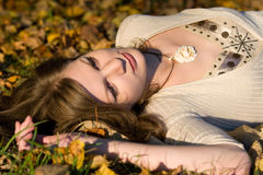 Girl in autunm leaves. Girl lying in autunm leaves on sunset time Royalty Free Stock Photos