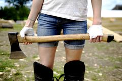 Girl with an axe. Girl with bandage protected hands holding an axe stock photo