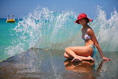 A girl and azure sea. Beautiful girl with rad hat enjoy the waves on pier. Crete, Greece Stock Images