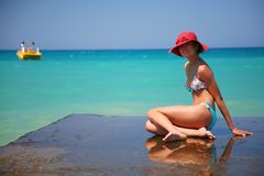 A girl and azure sea. Beautiful girl with rad hat enjoy sun on pier. Crete, Greece Royalty Free Stock Photos