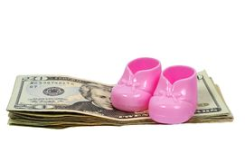 Girl Baby Booties Sitting on a Stack of  Money With Shadows. Horizontal shot of a pair of pink plastic baby booties sitting on top of a pile of twenty dollar Stock Photos