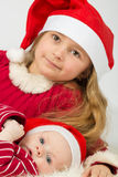 The girl with baby boy lie in the hats of Santa Claus Royalty Free Stock Photography