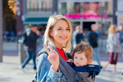 Girl with baby in carrier at street of Amsterdam. Young girl in jeans jacket and baby in carrier at street of Amsterdam. Holland, Netherlands. Autumn season stock photo