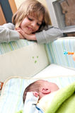 Girl and baby in crib. A little girl looking over the baby in the crib Royalty Free Stock Photo