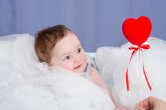 Girl-baby in the crib give heart. Six-month beautiful charming girl on the couch royalty free stock photos