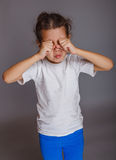 Girl baby cries rubs his eyes on a gray background Royalty Free Stock Photos