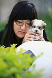 Girl and baby dog. In the garden Stock Photo