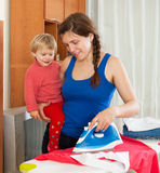 Girl with baby ironing Stock Images