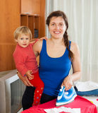 Girl with baby ironing Royalty Free Stock Photos