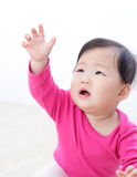Girl baby looking up and rise her arm Royalty Free Stock Photos