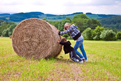 A girl with a baby on the mown field. Royalty Free Stock Photo