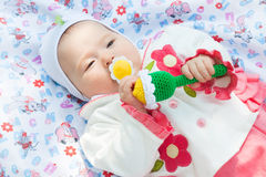 Girl baby a rattle played outdoors. A small beautiful girl baby a rattle played outdoors in the summer garden Stock Photography