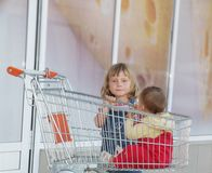 Girl and baby in shopping cart in supermarket Royalty Free Stock Images