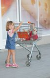 Girl and baby in shopping cart in supermarket Stock Photo
