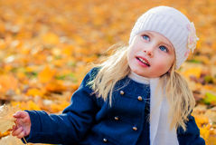 Girl. Baby girl sitting in autumn leaves Stock Photos