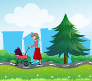 A girl with a baby stroller along the road Stock Photo