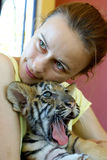 Girl with baby tiger. Young woman holding and hugging baby tiger Stock Photos