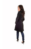 Girl from the back. A young Asian woman in a gray winter coat and jeans standing and looking Royalty Free Stock Photos